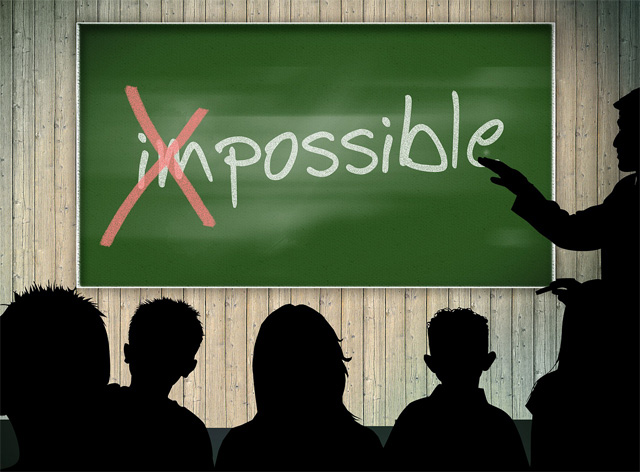 image of classroom chalkboard with 'impossible' written in chalk, the 'i' and 'm' have been crossed out to show the word 'possible'